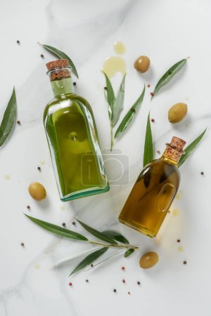 Photo for Top view of two bottles of olive oil and twigs on marble table - Royalty Free Image