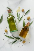 top view of two bottles of olive oil and twigs on marble table