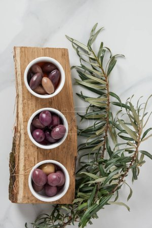 Photo for Top view of ingredients for olive oil preparation on log - Royalty Free Image