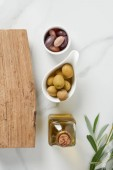top view of bottle of olive oil, log and olives in bowls on marble table