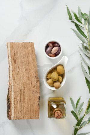 Photo for Elevated view of bottle of olive oil, log and olives in bowls on marble table - Royalty Free Image