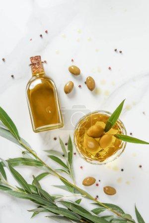Photo pour Vue de dessus de la bouteille et le verre d'huile d'olive sur la table de marbre - image libre de droit