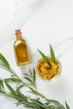 elevated view of bottle and glass with olive oil on marble tabletop