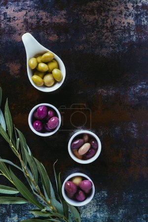 Photo for Top view of ingredients for olive oil and twigs on shabby surface - Royalty Free Image