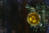 top view of glass of olive oil and twigs on marble table