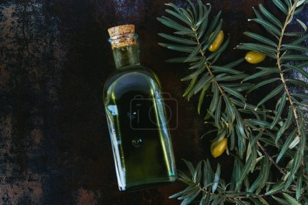 Photo for Top view of bottle of tasty olive oil, twigs and olives on shabby surface - Royalty Free Image