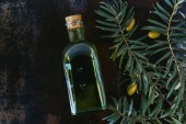 top view of bottle of tasty olive oil, twigs and olives on shabby surface