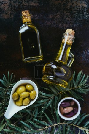 top view of two bottles of homemade olive oil and olives on shabby surface