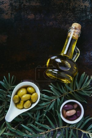 top view of yummy olives in bowls and bottles of olive oil on shabby surface