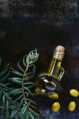 top view of bottle of olive oil, twigs and tasty olives on shabby surface