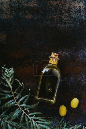 Photo for Elevated view of bottle of olive oil, twigs and appetizing olives on shabby surface - Royalty Free Image