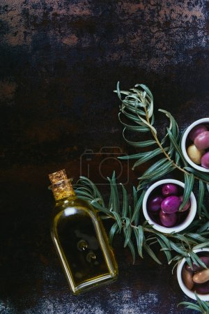 elevated view of different yummy olives and bottle of oil on shabby surface