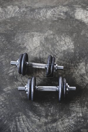 high angle view of adjustable dumbbells on concrete surface