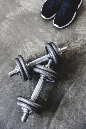 top view of adjustable dumbbells with sneakers on concrete surface