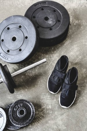 top view of barbell with weight plates and sneakers on concrete floor