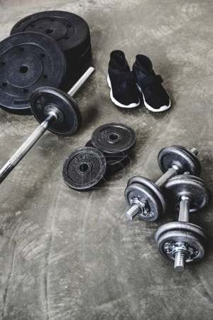 high angle view of various gym equipment and sneakers on concrete floor