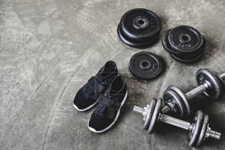 high angle view of dumbbells with weight plates and sneakers on concrete floor
