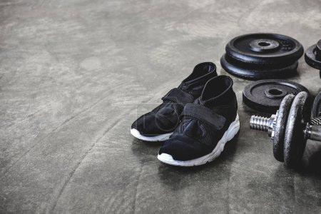 close-up shot of weight plates and sneakers on concrete floor