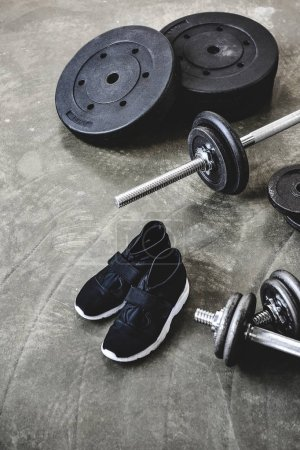 Photo for Dumbbells and barbell with weight plates and sneakers on concrete surface - Royalty Free Image