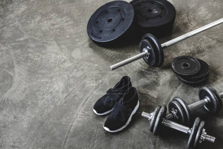 Photo for Dumbbells and barbell with weight plates and sneakers on concrete floor - Royalty Free Image