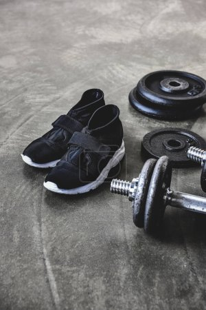 Photo for Close-up shot of dumbbells with weight plates and sneakers on concrete floor - Royalty Free Image
