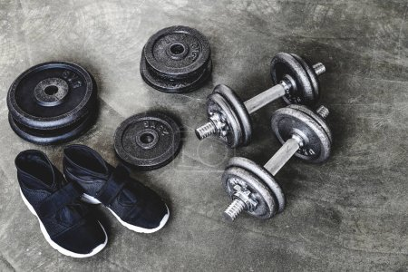 close-up shot of dumbbells with weight plates and sneakers on concrete surface