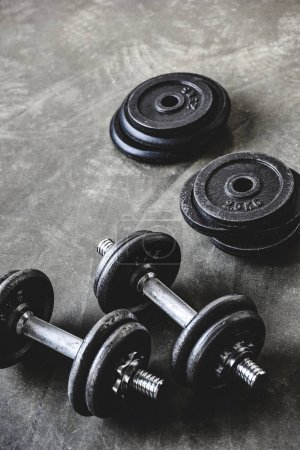 Photo for Close-up shot of dumbbells with weight plates on concrete surface - Royalty Free Image