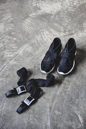 sneakers and wrist wraps on concrete surface