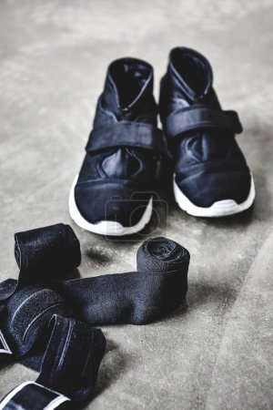 close-up shot of sneakers and wrist wraps on concrete floor