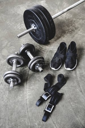 various weight lifting equipment on concrete surface