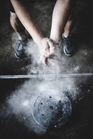 Photo for Cropped shot of power lifter clapping hands with talc before training - Royalty Free Image