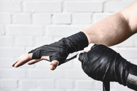 cropped shot of weight lifter wrapping hands before workout in front of white brick wall