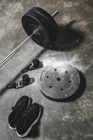 sneakers with wrist wraps and barbell on concrete surface