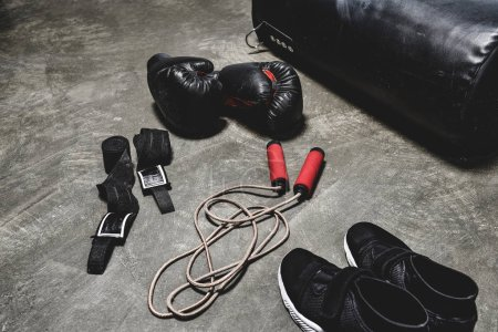various boxing equipment lying on concrete surface