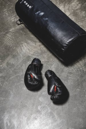 punching bag and boxing gloves on concrete surface