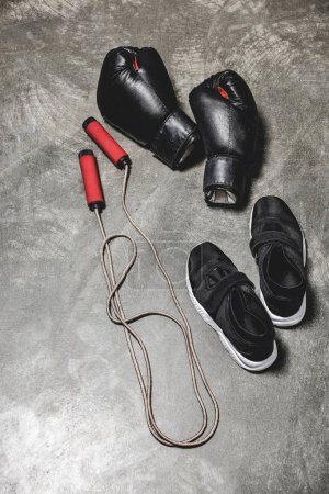 sporting shoes with jumping rope and boxing gloves on concrete surface