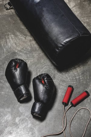 punching bag with jumping rope and boxing gloves on concrete surface