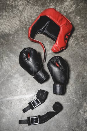 top view of boxing gloves and helmet with wrist wraps lying on concrete surface
