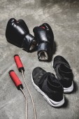 sneakers with jumping rope and boxing gloves on concrete surface