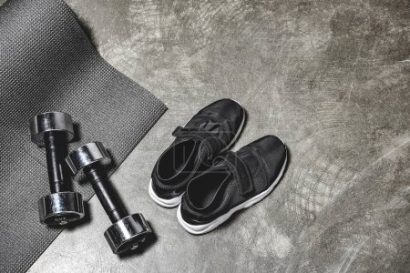 Photo for Top view of sporting shoes with yoga mat and dumbbells lying on concrete surface - Royalty Free Image