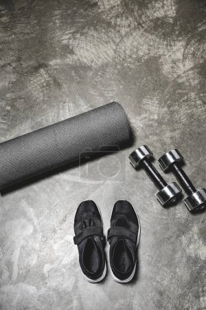 top view of sneakers with yoga mat and dumbbells lying on concrete surface