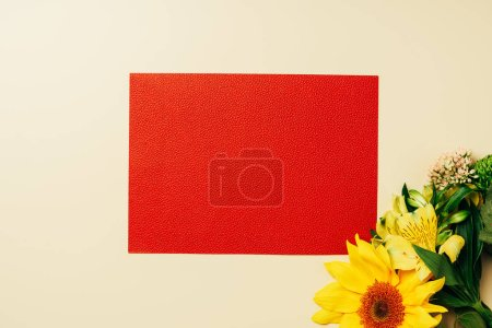 top view of empty red banner, arranged sunflower and lily flowers on beige backdrop