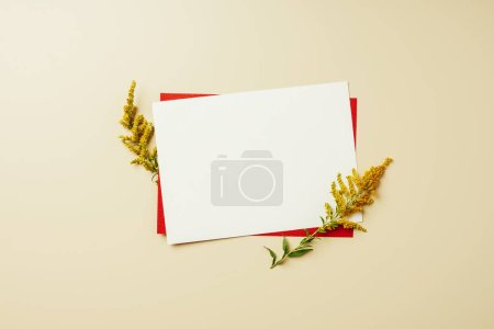 Photo for Flat lay with arrangement of red and white blank cards and wildflowers on beige backdrop - Royalty Free Image