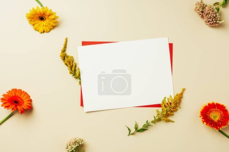 flat lay with arrangement of red and white blank cards and flowers on beige backdrop