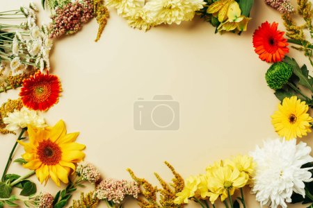 flat lay with various beautiful flowers arrangement with blank space in middle on beige background