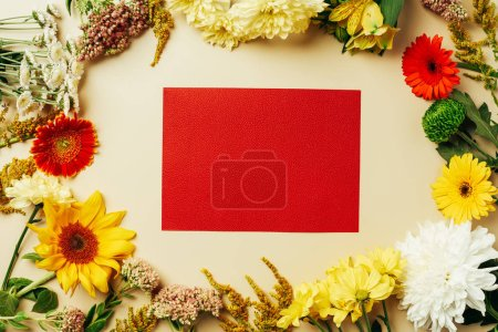 Photo for Flat lay with various beautiful flowers and blank red card on beige background - Royalty Free Image
