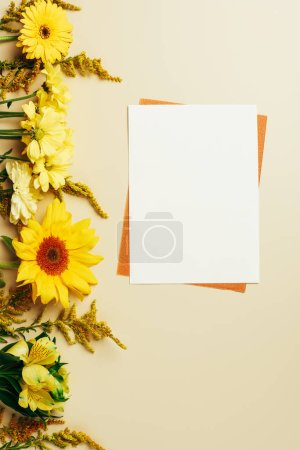 flat lay with bright flowers, empty white and orange cards on beige background