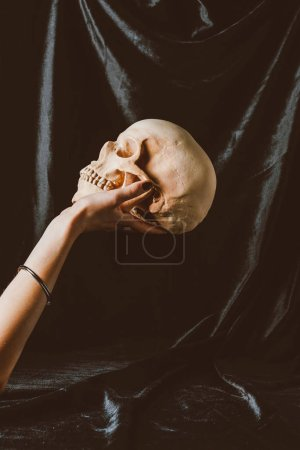 cropped view of woman holding halloween skull on black cloth