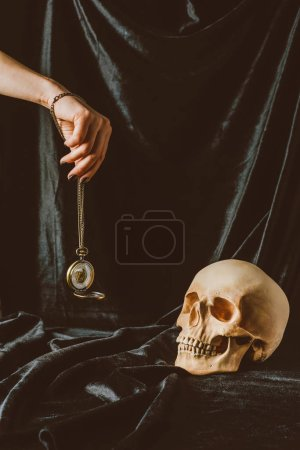 cropped view of woman holding vintage clock on the chain near skull on black cloth
