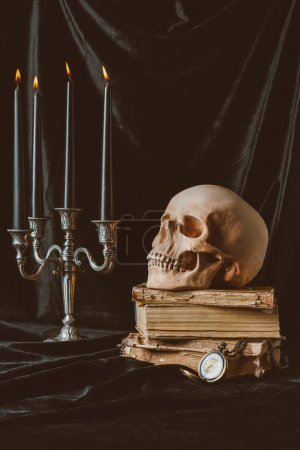 black halloween candles, skull and ancient books on black cloth